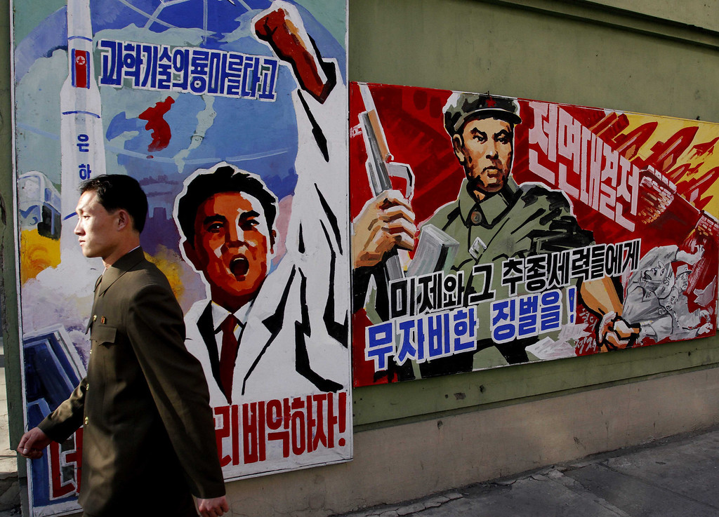 ". A North Korean man walks past propaganda posters in Pyongyang, North Korea, on Tuesday, March 26, 2013, that threaten punishment to the ""U.S. imperialists and their allies.\"" The U.S. recently tightened sanctions against North Korea after Pyongyang tested a nuclear device in February in defiance of international bans against atomic activity. (AP Photo/Kim Kwang Hyon)"