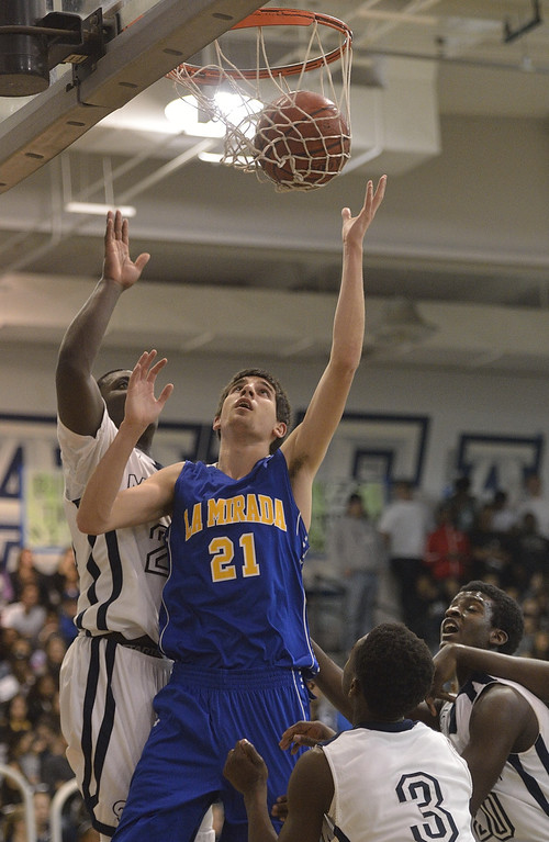. LAKEWOOD, CALIF. USA -- La Mirada\'s Charlie Reid (21) and Mayfair\'s Brandon Reynolds (20) go after a rebound in Lakewood, Calif., on February 8, 2013. Mayfair defeated La Mirada 60 to 59. Photo by Jeff Gritchen / Los Angeles Newspaper Group