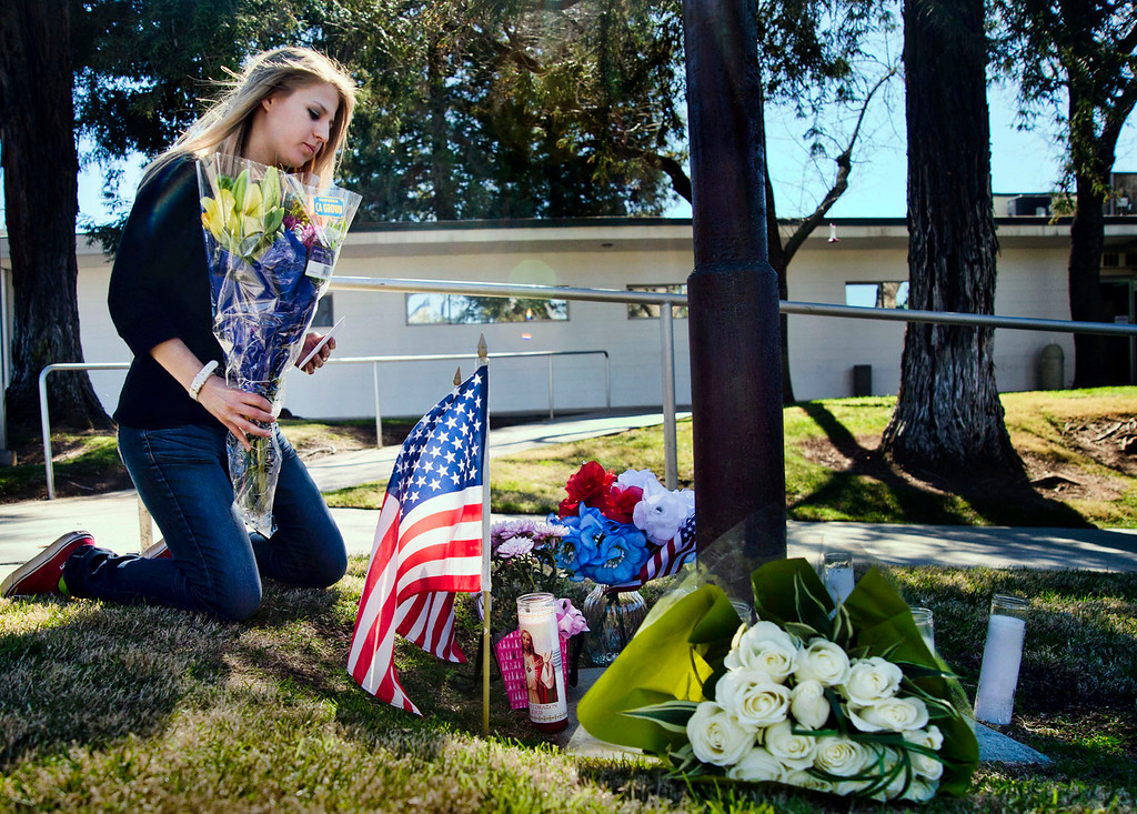 . Christine Harper, 19, of Yucaipa, brings flowers to the makeshift memorial for the slain San Bernardino Sheriff\'s deputy at the Yucaipa Station on Wednesday, Feb. 13, 2013. The deputy was killed during a shootout with ex-LAPD officer Christopher Dorner in Big Bear yesterday.  (SGVN/Staff photo by Watchara Phomicinda)