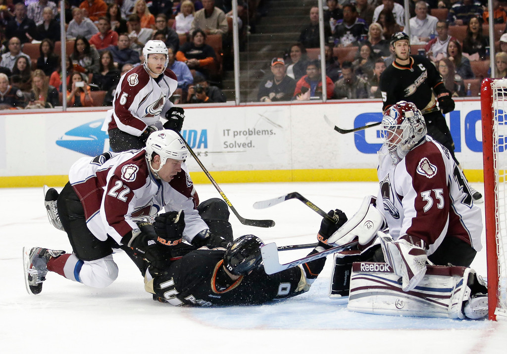 . Anaheim Ducks\' Corey Perry(10) and Colorado Avalanche\'s Matt Hunwick(22) fall to the ice as Colorado Avalanche goalie Jean-Sebastien Giguere(35) watches during the second period of an NHL hockey game in Anaheim, Calif., Wednesday, April 10, 2013. (AP Photo/Jae C. Hong)
