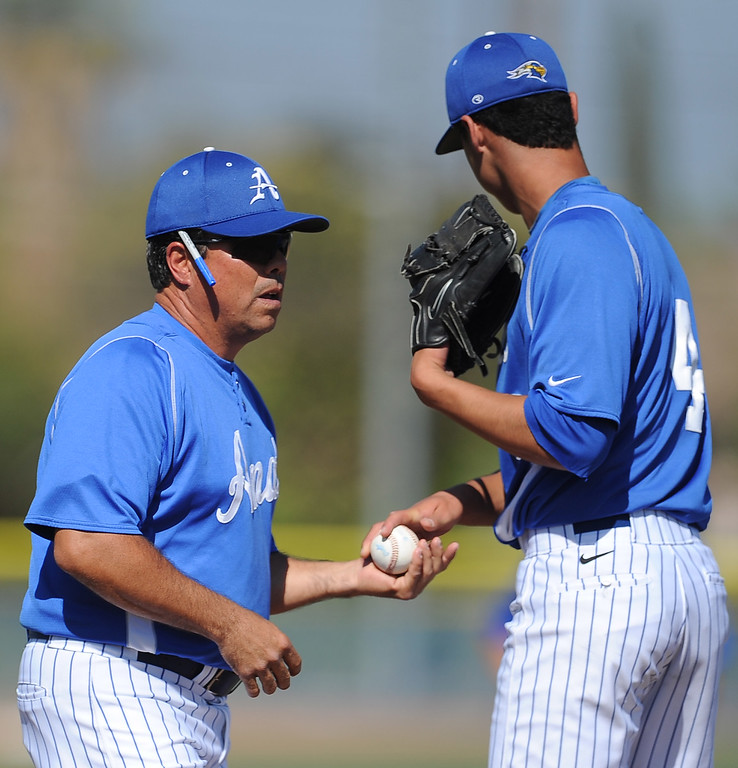 . Bishop Amat head coach Andy Nieto takes the ball from starting pitcher Alex Garcia (4) in the second inning of a prep baseball game against St. Paul at Bishop Amat High School on Friday, April 19, 2012 in La Puente, Calif. Bishop Amat won 3-2.    (Keith Birmingham/Pasadena Star-News)