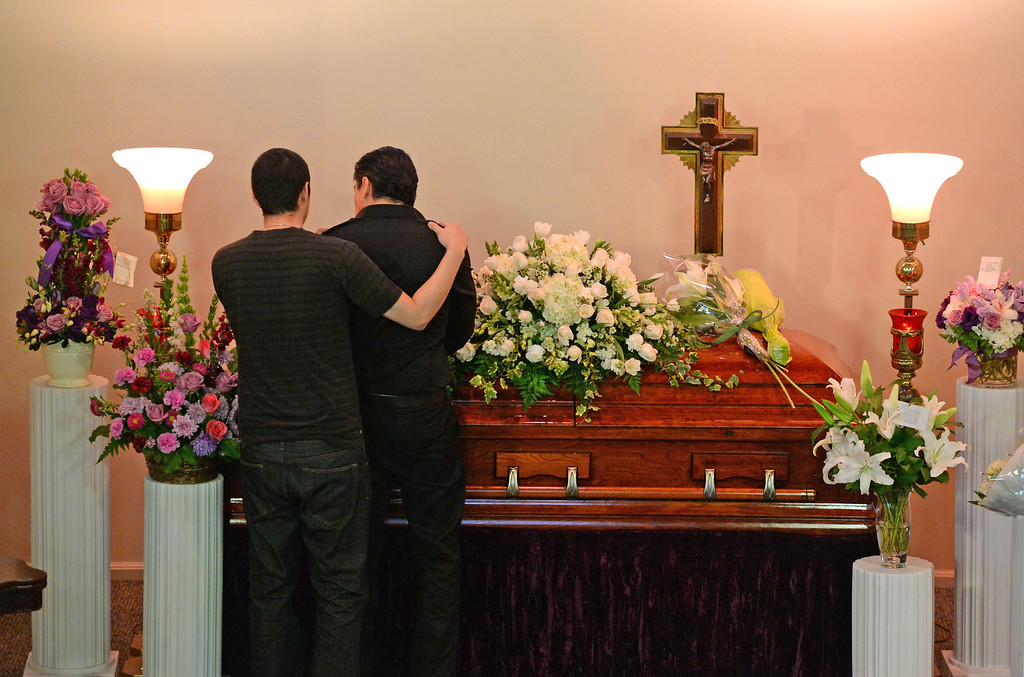 . Funeral services were held for Torrance High student Valentina d\'Alessandro Wednesday, December 11, 2013, in Torrance, CA.  Valentina\'s brotherLuca, left, hugs family and friends after the ceremony by the casket. D\'Alessandro was killed in a traffic collision in Wilmington Saturday. Photo by Steve McCrank/DailyBreeze