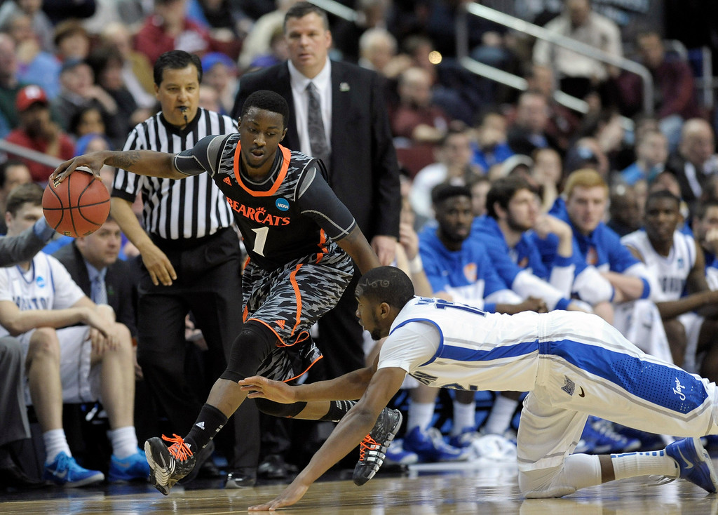 . Cincinnati\'s Cashmere Wright, left, dribbles past a diving Creighton\'s Jahenns Manigat during the first half of a second-round game of the NCAA college basketball tournament, Friday, March 22, 2013, in Philadelphia. (AP Photo/Michael Perez)