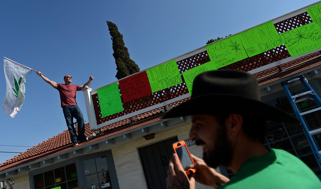 Description of . George Lanzas, 33, of Hesperia and the manager of Doc Holliday's Collective, in Mentone, uses his phone to photograph the collectives' owner, Luke Luce, as supporters protest the closure of the medical marijuana dispensary Monday August 12, 2013.  (Photo by Rick Sforza/Redlands Daily Facts)