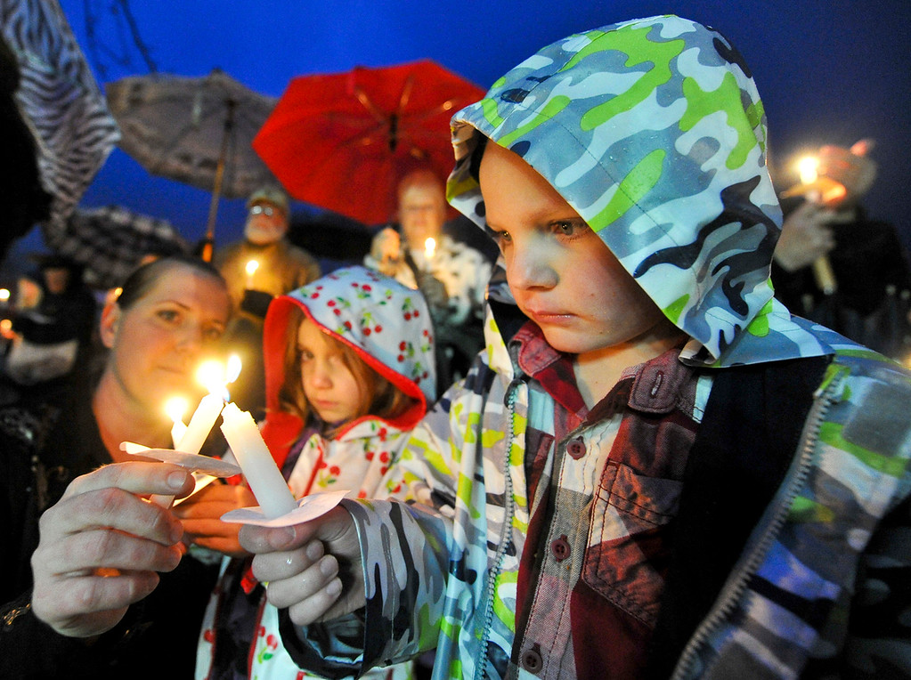 . John Mongez, 5,  watches his candle get lit  in the rain by his mother Rhiannon Mongez, of Beaumont, during a candlelight vigil in honor of fallen San Bernardino County Sheriff\'s Detective Jeremiah MacKay at the Yucaipa Community Center in Yucaipa, Calif. on Tuesday, Feb. 19, 2013. MacKay was killed by fugitive ex-cop Christopher Dorner on Feb. 12 during a fiery shootout in which Dorner barricaded himself in a cabin near Big Bear. (Rachel Luna / Staff Photographer, San Bernardino Sun)
