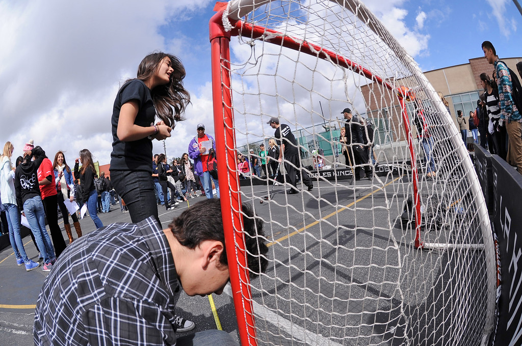 . DaVinci students measure the angles of a shot to the goal. Raytheon Space and Airborne systems engineers teamed up with LA Kings players Justin Williams, #14, and Willie Mitchell #33 at DaVinci High School in Hawthorne to learn about geometry and how it plays into the game of hockey.   Photo by Brad Graverson 3-8-13