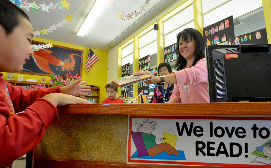 . 04-25-2013-(LANG Staff Photo by Sean Hiller)- Due to five consecutive years of deep budget cuts, all of the libraries in the district\'s 17 elementary schools are run by parent volunteers. Parent volunteers Cathy Shinozaki,right, and Laura Hamano, back left, check out books to students at Lincoln Elementary School.