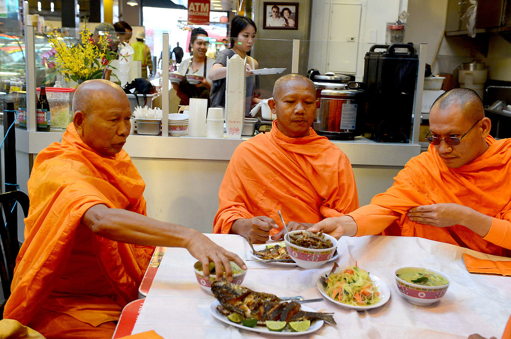 Description of . After blessing the opening of Sticky Rice at Grand Central Market in downtown Los Angeles Monday, April 30, 2013 Wat Thai Temple monks, of North Hollywood, are served their food. Sticky Rice, owned by David Tewasart, of Pasadena, is kicking off the openings of new restaurants at the market. (SGVN/Staff Photo by Sarah Reingewirtz)