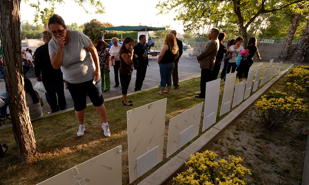 Description of . People view a row of posters commemorating the lives of homicide victims during the annual Victims Candlelight Vigil at the police station in San Bernardino April 23, 2013.   GABRIEL LUIS ACOSTA/STAFF PHOTOGRAPHER.
