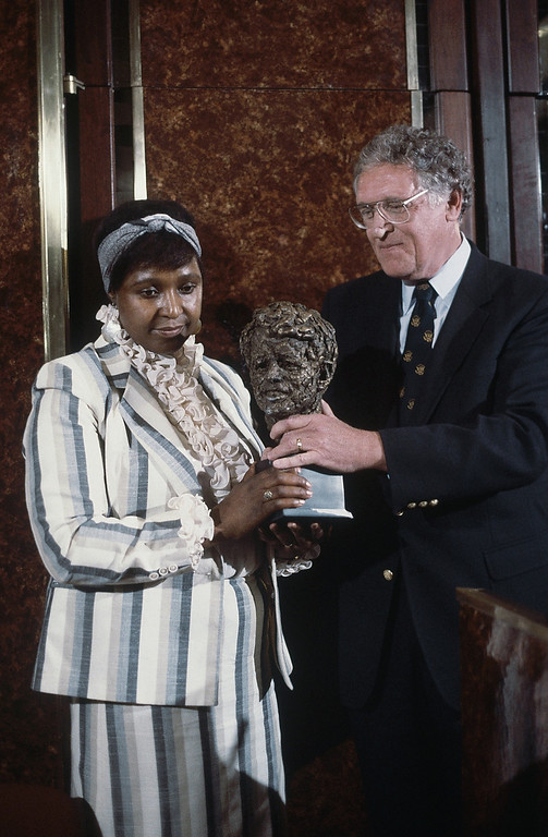 . Winnie  Mandela, wife of African Guerrilla leader Nelson Mandela, in Johannesburg, South Africa, when she receives the Robert Kennedy human rights award Jan. 24, 1986. Man at right is unidentified. (AP Photo/Greg English)