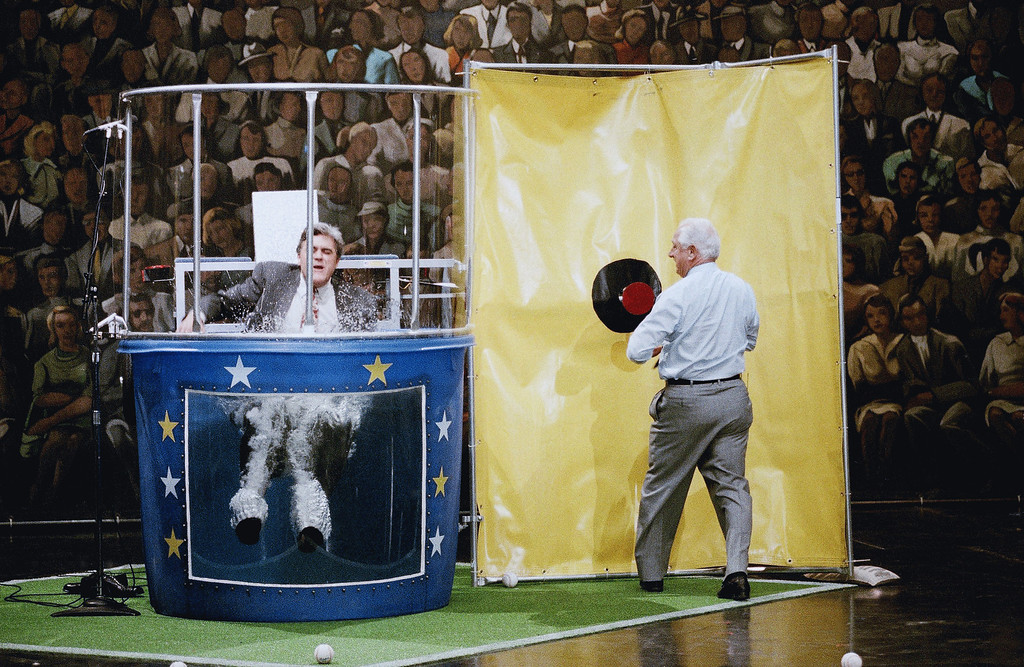 ". LENO SHOW 1993  ""The Tonight Show\"" host Jay Leno, left, falls in to the water tank as Los Angeles Dodgers\' manager Tommy Lasorda pushes the mark after missing it numerous times during taping of the show, June 3, 1993 in Burbank, Calif. Leno lost a bet to Lasorda that the Dodgers would win ten straight. (AP Photo/Kevork Djansezian)"