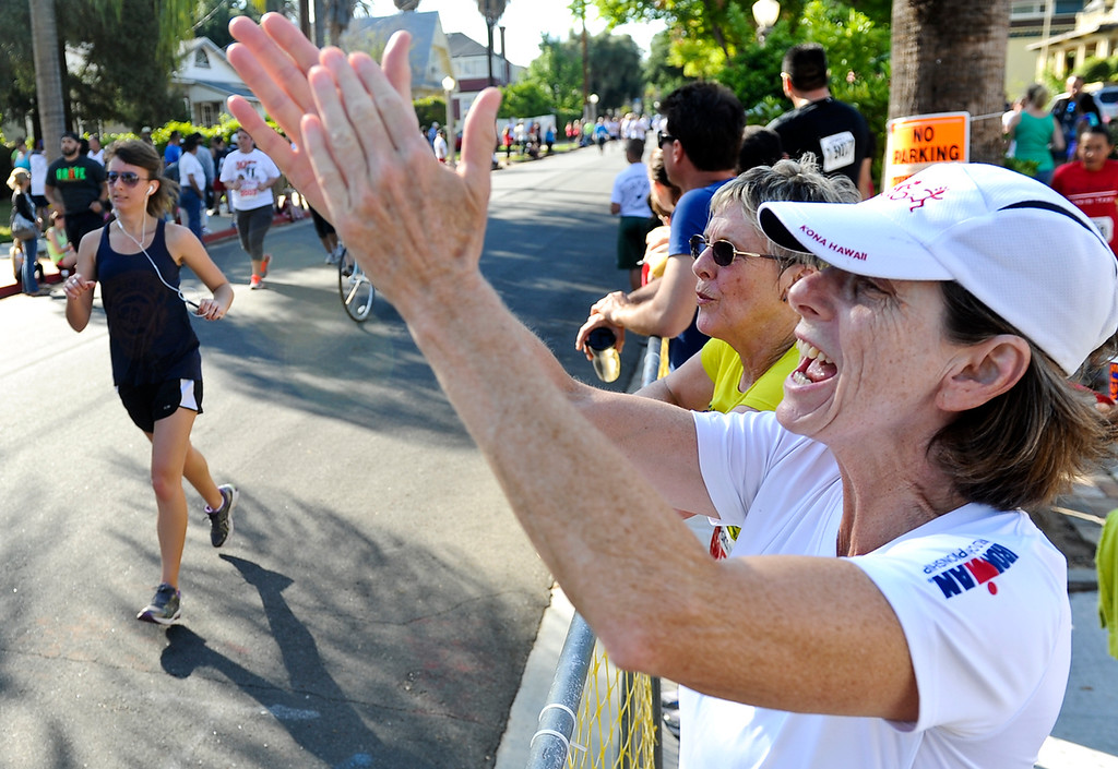 Description of . Runners are cheered on as they get to the finish line in the 30th annual Run Through Redlands race in Redlands on Sunday, April 21, 2013. The race proceeds benefited the Kiwanis Club Foundation and scholarship opportunities for high school seniors. (Rachel Luna / Staff Photographer)