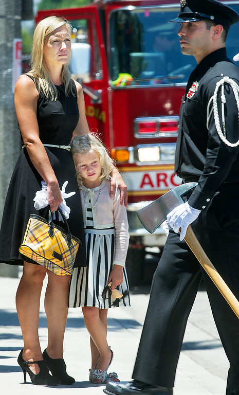 Description of . Brigitte Herdman and daughter Sienna watching Michael Herdman coffin being loaded in hurst at memorial service on Wednesday, July 9, 2014, for the Arcadia firefighter-paramedic found dead in the Los Padres National Forest last Friday. Herdman, an avid adventurer, died after becoming separated from his camping partner. He fell from a cliff and was killed by his injuries. Searchers canvassed the forest for 11 days before finding his body.(Photo by Walt Mancini/Pasadena Star-News)