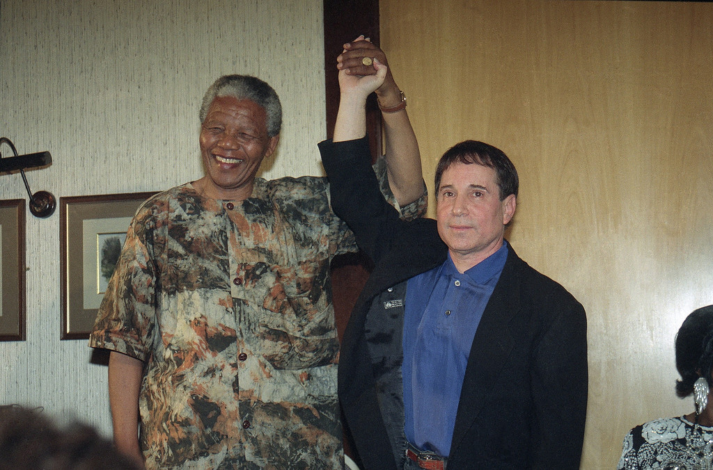 . Nelson Mandela the president of African National Congress claps hands with American singer and songwriter Paul Simon in a gesture that signals the end of the boycott imposed by anti-Apartheid organizations, at a function held in Simon honour in Johannesburg, South Africa Friday, Jan. 10, 1992. (AP Photo/ Adil Bradlow)