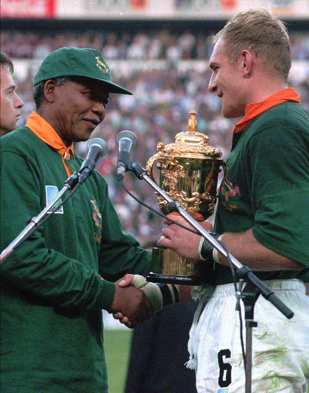 . This June 24, 1995, file photo shows South African rugby captain Francios Pienaar, right, receiving the Rugby World Cup trophy from President Nelson Mandela, left, who wears a South African rugby shirt, after South Africa defeated New Zealand in the finals in Johannesburg. Fifteen years later, another World Cup on South African soil has the power to shape the country anew.  (AP Photo / Ross Setford, File)