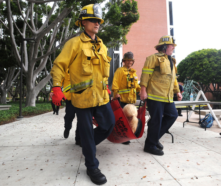 . A multi-agency response exercise to an active shooter and mass casualty incident was held Tuesday on the Cal State Long Beach campus.  Long Beach firefighters evacuate the victims under protection from campus police to a triage center. 20130813 Photo by Steve McCrank / Staff Photographer