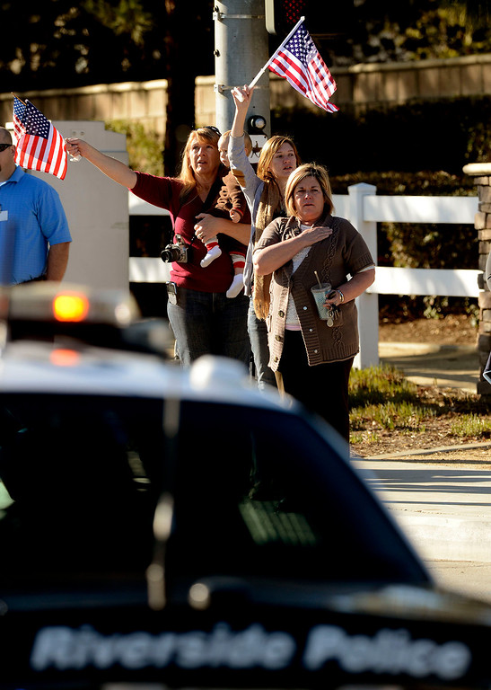 Description of . Sara Amend, with grandson Lochlain, Laura Amend, and Sharon Kerns salute a police procession for Riverside Police Officer Michael Crain along Trautwein Road in Riverside February 13, 2013.  Crain was shot and killed last week by fugitive Christopher Dorner in Riverside.  GABRIEL LUIS ACOSTA/STAFF PHOTOGRAPHER.