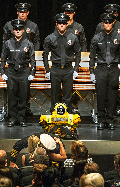 Description of . Arcadia Fire Chief Kirt Norwood after giving Brigitte Herdman the American Flag that draped the coffin of her husband, he gives her a warm embrace during Michael Herdman memorial services Wednesday, July 9, 2014, for the Arcadia firefighter-paramedic found dead in the Los Padres National Forest last Friday. Herdman, an avid adventurer, died after becoming separated from his camping partner. He fell from a cliff and was killed by his injuries. Searchers canvassed the forest for 11 days before finding his body.(Photo by Walt Mancini/Pasadena Star-News)
