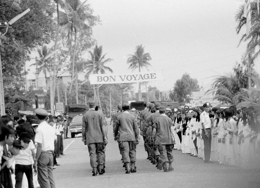 . A bon voyage banner stretches overhead in Da Nang, South Vietnam, as soldiers march down a street following a farewell ceremony for some of the last U.S. troops in the country\'s northern military region, March 26, 1973.  About 800 men are still stationed in Da Nang and are to remain there until the release of the American POWs is completed.  (AP Photo)
