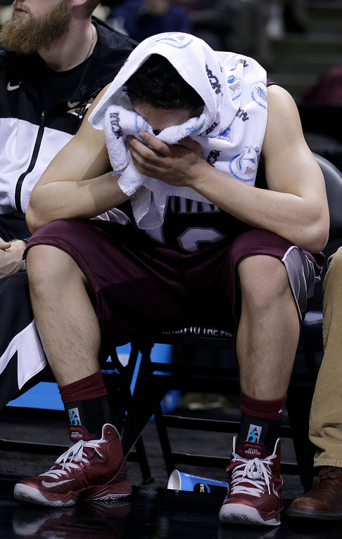 . Montana guard Jordan Gregory covers his face as he sits on the bench during the second half of a second-round game in the NCAA college basketball tournament against Syracuse in San Jose, Calif., Thursday, March 21, 2013. Syracuse won 81-34. (AP Photo/Ben Margot)