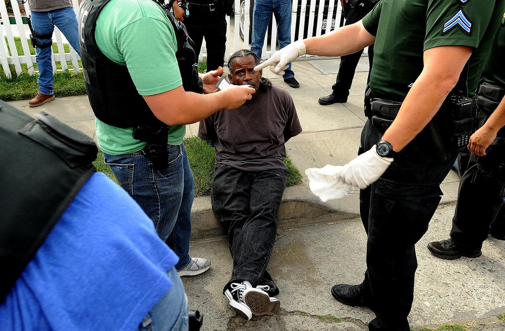 Description of . An unidentified man is detained because of a probation violation along the 1200 block of N. Genevieve Street in San Bernardino April 4, 2013.   GABRIEL LUIS ACOSTA/STAFF PHOTOGRAPHER.