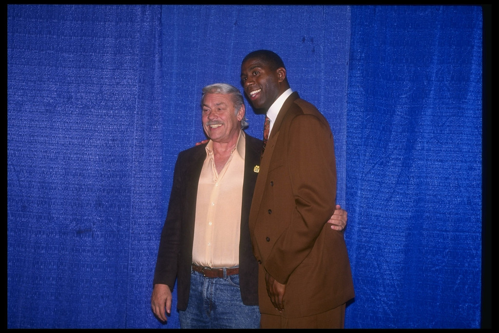 ". INGLEWOOD, CA - FEBRUARY 16: Guard Earvin ""Magic\"" Johnson #32 of the Los Angeles Lakers at his retirement ceremony with Lakers owner Jerry Buss on February 16, 1992 at the Great Western Forum in Inglewood, California.  (Photo by Ken Levine/Getty Images)"
