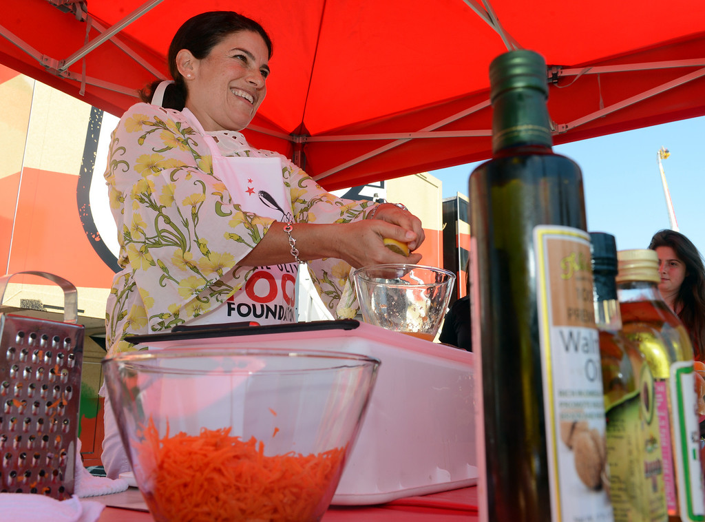 ". Program Trainer Lisa Fontanesi shows kids how to make quick easy snacks outside the Jamie Oliver Food Foundation\'s ""Big Rig Teaching Kitchen\"" at the L.A. County Fair at Fairplex in Pomona. (Jennifer Cappuccio Maher/Inland Valley Daily Bulletin)"