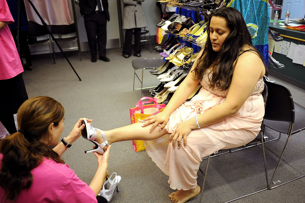 . Elidia Padilla tries on shoes during Operation School Bell\'s annual Prom Day event at the Assistance League of Los Angeles Thursday March 7, 2013.  Fifty-five homeless or needy LAUSD high school girls were able to select a dress, shoes and accessories during the event.(Andy Holzman/Los Angeles Daily News)