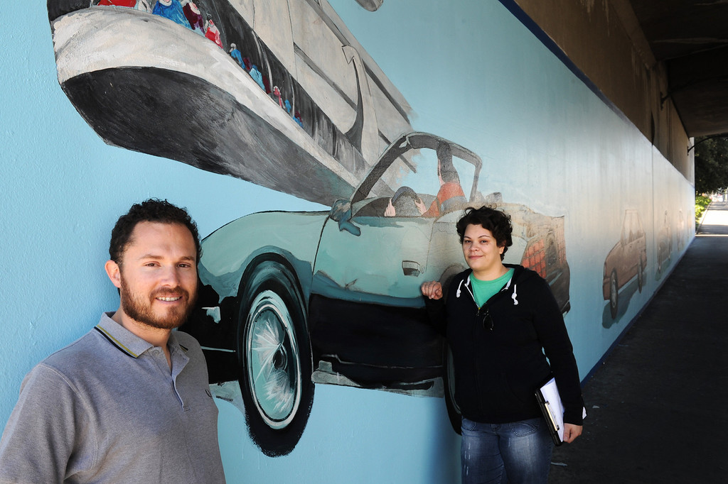 ". Elijah Flores, left, and Erika Tachet, are making a documentary film of their grandfather, muralist Alfredo Diaz Flores, and the restoration of his mural ""Panorama: G.M. Recollections from the Past,\"" on Van Nuys Boulevard in Panorama City. (Michael Owen Baker/Staff Photographer)"