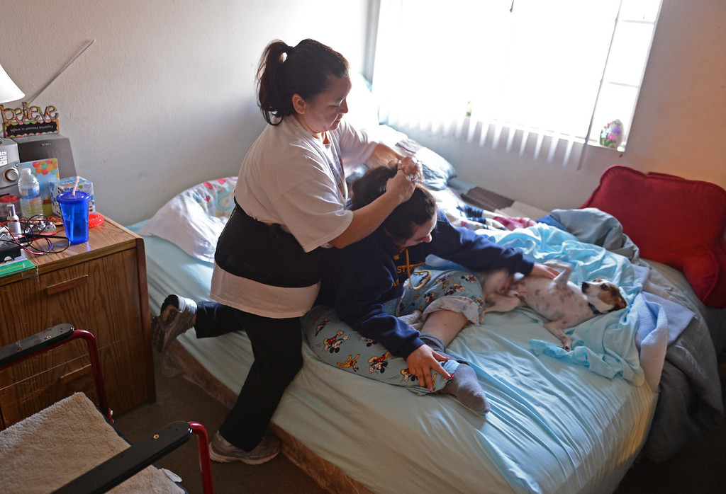 . Longtime caregiver Lucky Puertas has been with Olivia for over 20 years. Here, she wakes her up and readies her for her day. Photo by Brad Graverson/LANG 1-29-13