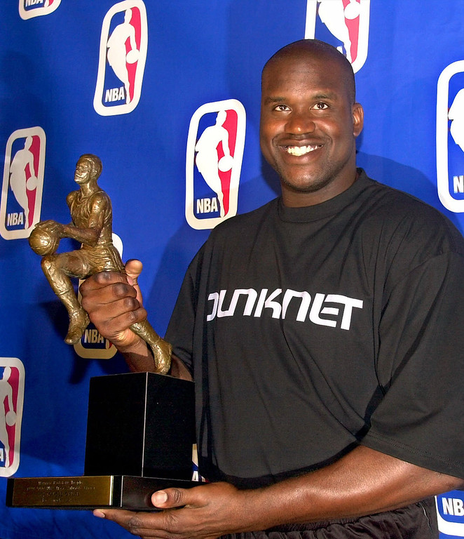 . Los Angeles Lakers center Shaquille O\'Neal smiles as he holds the Maurice Podoloff Trophy after being named the NBA\'s Most Valuable Player of the 1999-2000 season during ceremonies Tuesday, May 9, 2000, in Los Angeles.  O\'Neal, who led the league in scoring (29.7 points per game) and field goal percentage (.574), took all but one of the 121 first-place votes of U.S. sports writers.  (AP Photo/Nick Ut)