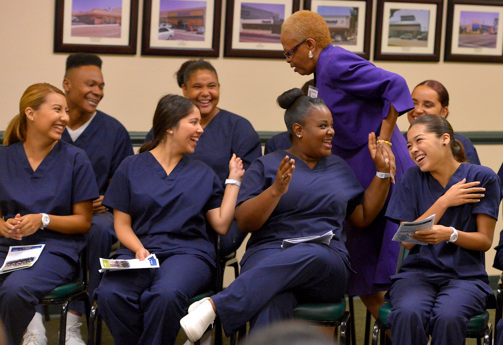 . Before giving a graduation address, Sharon Cruse recieves high-fives from the 10 recent high school graduates who received their Certified Nursing Assistant certificates at the Goodwill in Long Beach, CA on Friday, August 22, 2014. The students; Gabriela Avila, Averianna Burnett, Alesia Clay, Ariana Mays, Kendra Montano, Silvia Monzon, Genesis Perez, Cindia Sanchez, Daniel Scott and Dahlia You completed the year-long course in a partnership between the LBUSD and Goodwill. This is the first year that the state Certified Nurse Assistant Training Academy program has been free for the students. It was announced to the families and friends gathered that all 10 of the graduates have health care job interviews next week. (Photo by Scott Varley, Daily Breeze)