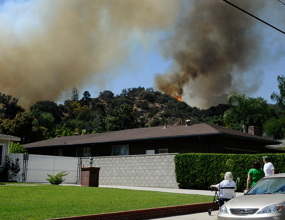 Description of . April 20,2013. MONROVIA. Local neighbors keep their eyes on a brush fire in the hillside of north Monrovia grew to 150 acres and prompted mandatory evacuations Saturday afternoon, officials said. The fire, which ignited shortly after 11 a.m. in the 300 block of Madison Ave. was 10 percent contained as of 3 p.m.. Photo by Gene Blevins/LA Daily News