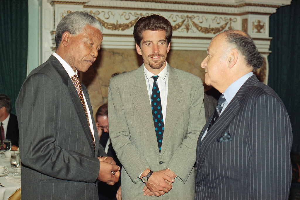. African National Congress leader Nelson Mandela, working to woo foreign corporations back to South Africa since he renounced anti-apartheid economic sanctions last week, chats with Mauric Templesman, right, of the diamond trading firm Templesman & Son, and John F. Kennedy Jr. during a visit with officers and friends of the South Africa Free Elections Fund in New York,  Sept. 28, 1993. (AP Photo/Justin Sutcliffe)