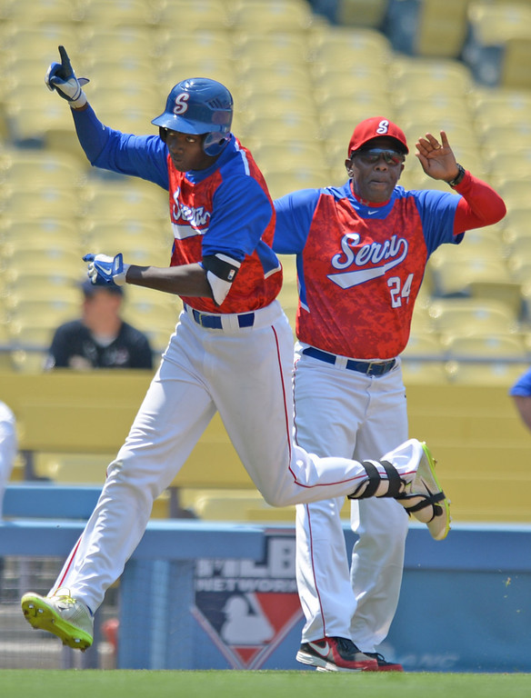 . Serra\'s Marcus Wilson (8) celebrates as he rounds third with coach Wil Aaron after hitting a home run against Mira Costa in the CIF-SS Division III championship baseball game Friday at Dodger Stadium. Serra won the title, 8-1. 20130531 Photo by Steve McCrank / Staff Photographer