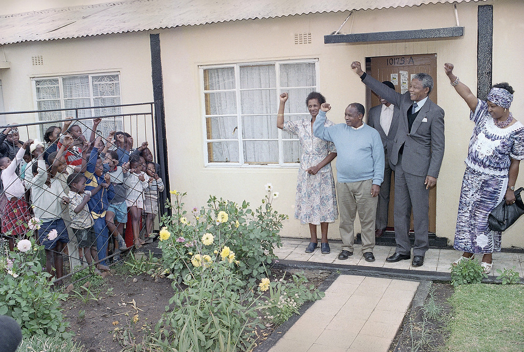 . Nelson Mandela and Winnie Mandela, right, and Elias and Caroline Motsoaladi, return black power salute to local children outside the Motsoaladi house, Soweto Wednesday, Feb. 14, 1990. Mandela was visiting his old friend with whom he spent many years in jail. Motsoaladi was one of the six ANC leaders released from prison on Oct. 1989. Mandela was released last Sunday. (AP Photo/John Parkin)