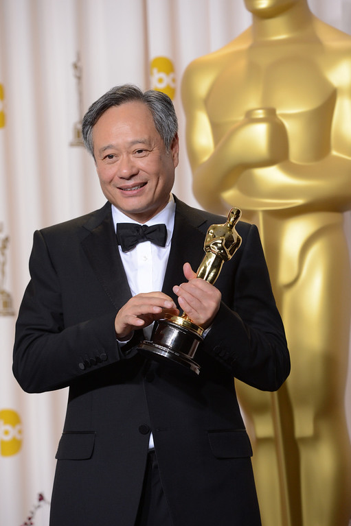 Description of . Ang Lee poses with his award for best directing for