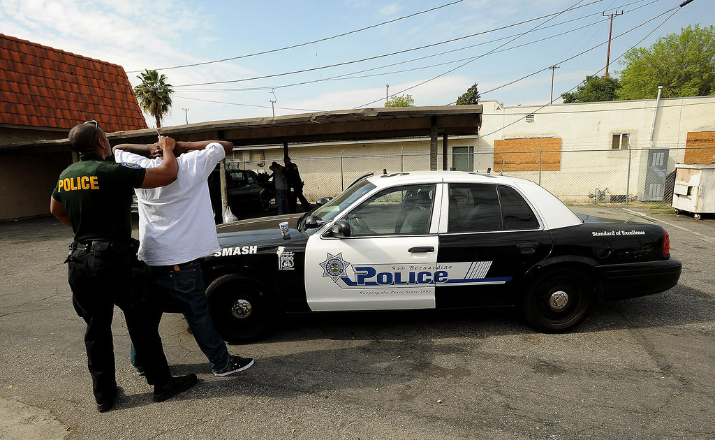 Description of . An unidentified man is detained during a SMASH sweep along the 1200 block of N. Genevieve Street in San Bernardino April 4, 2013.   GABRIEL LUIS ACOSTA/STAFF PHOTOGRAPHER.