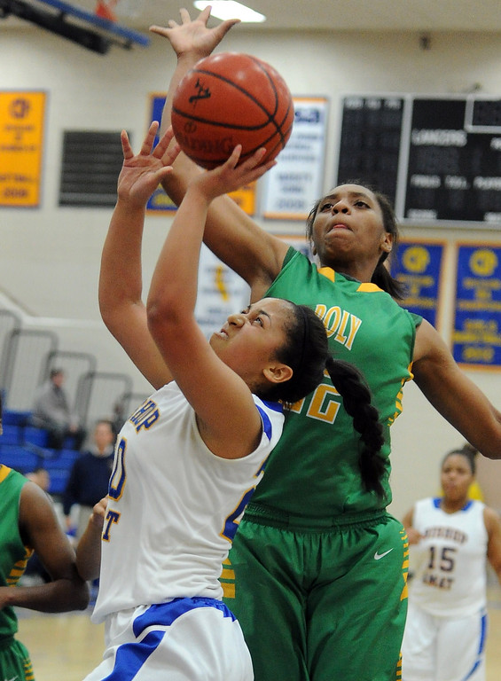 Description of . Long Beach Poly's Jada Matthews (22) blocks the shot of Bishop Amat's Janae Chamois in the first half of a CIF State Southern California Regional semifinal basketball game at Bishop Amat High School on Tuesday, March 12, 2013 in La Puente, Calif. Long Beach Poly won 52-34.  (Keith Birmingham Pasadena Star-News)