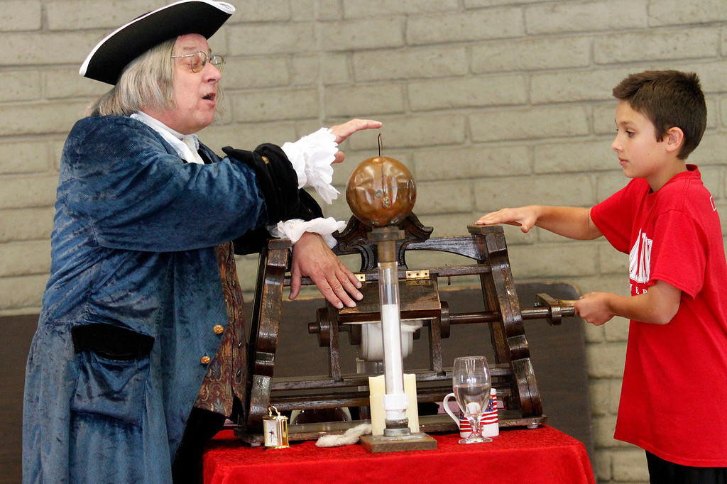 ". Lucas Valero, 10, assists Benjamin Franklin with his ""Electrostatic Generator,\"" during Ben Franklin\'s Colonial Assembly: A Museum On Wheels, at St. Marks Luthern School, in Hacienda Heights, Thursday, March 28, 2013. (Correspondent Photo by James Carbone/HIGH)"