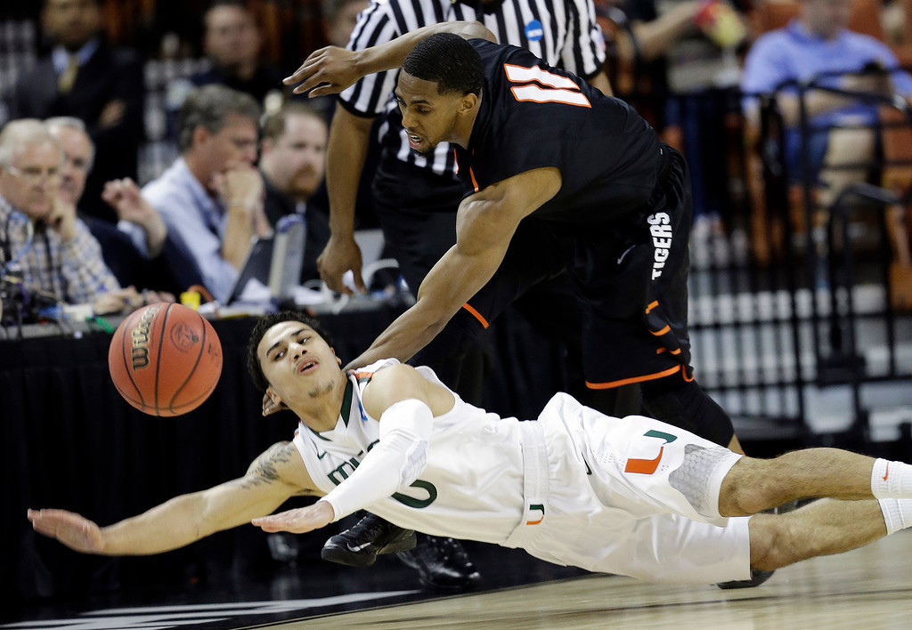 . Pacific\'s Lorenzo McCloud (11) and Miami\'s Shane Larkin (0) battle for a loose ball during the first half of a second-round game of the NCAA college basketball tournament Friday, March 22, 2013, in Austin, Texas.  (AP Photo/David J. Phillip)