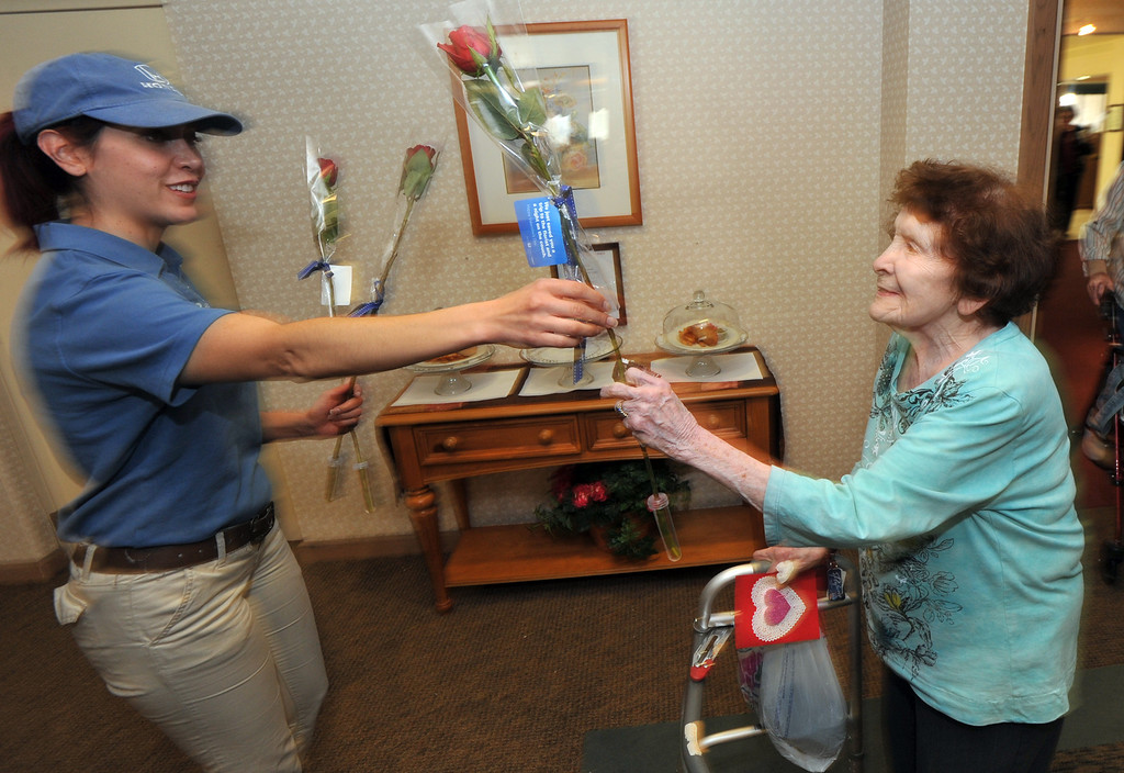 Description of . Tamara Torres, with Honda, gives resident, Ida Gomez, a receive long-stem red rose on Valentine's Day at Merill Gardens in Whittier on Thursday February 14, 2013. The Helpful Guys in Blue, a group sponsored by the Southern California Honda Dealers Association surprise Whittier residents with a complimentary red roses. (SGVN/Staff Photo by Keith Durflinger)