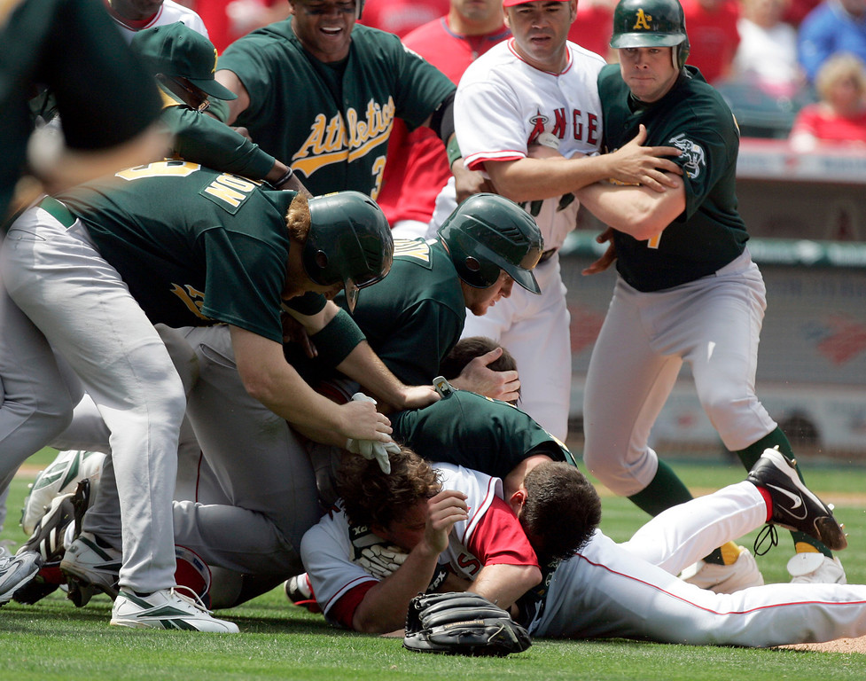 . Los Angeles Angels starting pitcher John Lackey, bottom, and catcher Jeff Mathis, hidden, brawl with Oakland Athletics\' Jason Kendall after Kendell rushed the mound during the sixth inning of their baseball game Tuesday, May 2, 2006, in Anaheim, Calif. Lackey threw a pitch to Kendall in the sixth inning that started out high and inside, then sharply broke back toward the plate. Kendall backed out of the batter\'s box, then suddenly charged the mound after Lackey barked something at him. The two grabbed each other as they both tumbled to the ground. Lackey and Kendall were ejected from the game. (AP Photo/Chris Carlson)