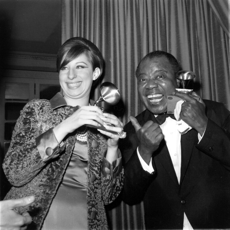 ". Actress-singer Barbra Streisand and jazz trumpeter-singer Louis Armstrong hold their Grammy trophies at the 7th annual Grammy Awards in New York City, April 13, 1965. Streisand won Best Vocal Performance, Female, for ""People,\"" and Armstrong won Best Vocal Performance, Male, for \""Hello Dolly!\"" (AP Photo)"