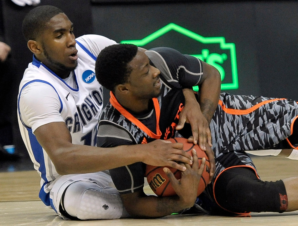 . Creighton\'s Jahenns Manigat, left, and Cincinnati\'s Cashmere Wright wrestle for a loose ball during the second half of a second-round game of the NCAA college basketball tournament, Friday, March 22, 2013, in Philadelphia. Creighton won 67-63. (AP Photo/Michael Perez)