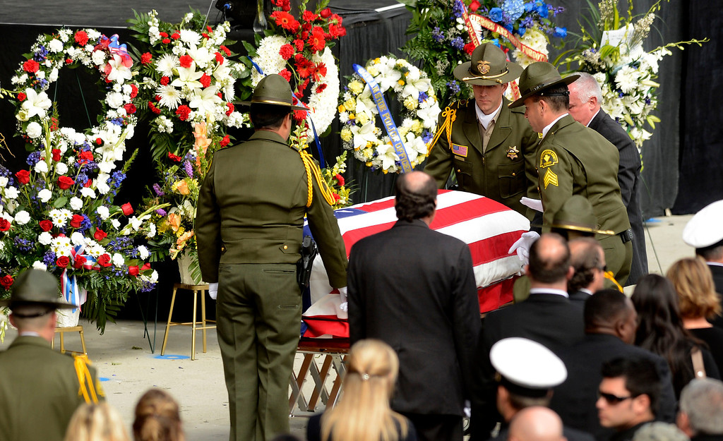 Description of . San Bernardino County Sheriff Deputies tend to the casket of SBCO Sheriff Deputy Jeremiah MacKay during memorial services at the San Manuel Amphitheater in Devore February 21, 2013.  GABRIEL LUIS ACOSTA/STAFF PHOTOGRAPHER.
