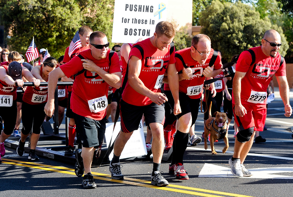 Description of . A team of runners, representing Crossfit Redlands, pushes a  bobsled in honor of the Boston boming victims during the 30th annual Run Through Redlands race on Sunday, April 21, 2013. The race proceeds benefited the Kiwanis Club Foundation and scholarship opportunities for high school seniors. (Rachel Luna / Staff Photographer)