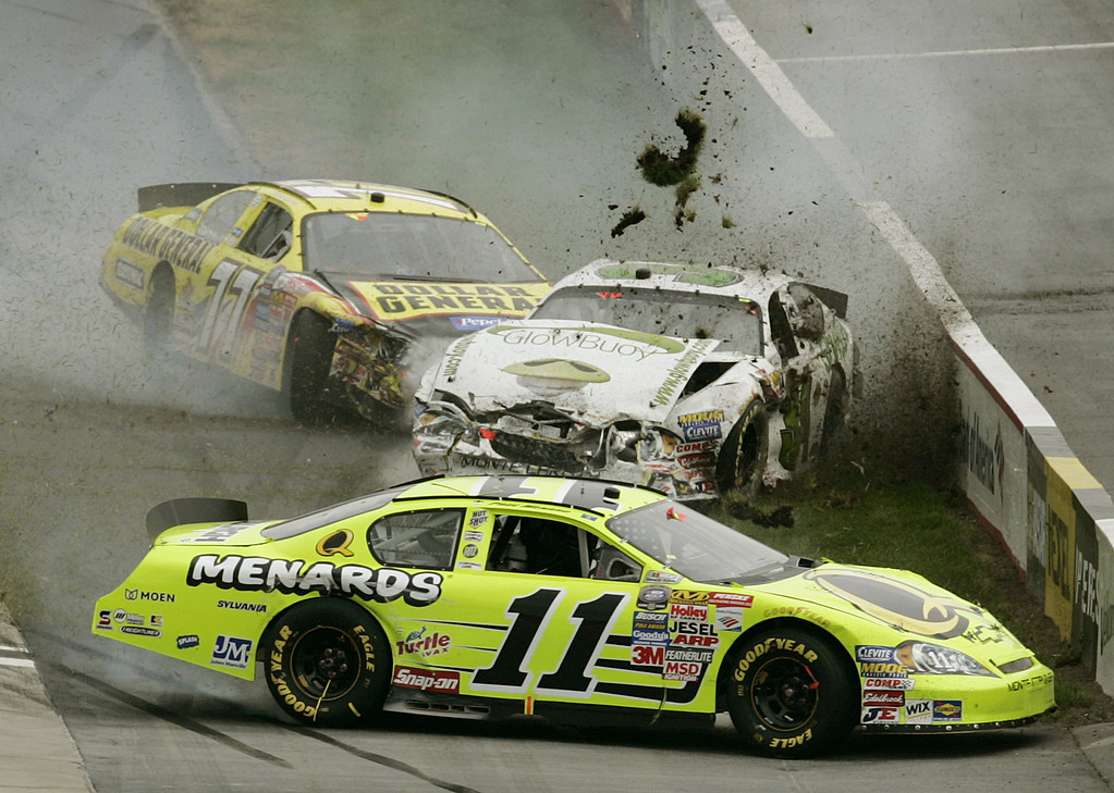 . Dirt and mud fly as NASCAR Busch drivers Paul Menard, bottom, Todd Bodine, center, and Burney Lamar, top, smack up during the Stonebridgeracing.com 200  Saturday, June 3, 2006 at the Dover Speedway in Dover, Del. The drivers were not injured in the crash. (AP Photo/Chris Gardner)