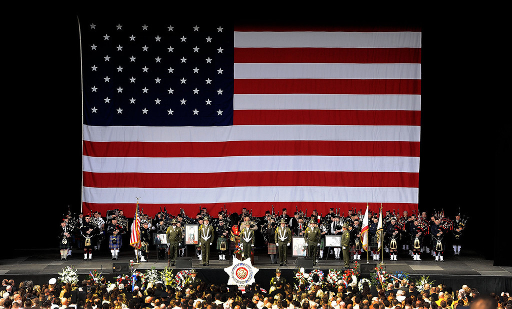 Description of . An American flag hangs above the stage during memorial services for San Bernardino County Sheriff Deputy Jeremiah MacKay at the San Manuel Amphitheater in Devore February 21, 2013.  GABRIEL LUIS ACOSTA/STAFF PHOTOGRAPHER.