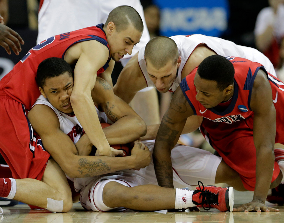 . Mississippi guard Marshall Henderson, left, tries to steal the ball from Wisconsin guard George Marshall, bottom left, during the second half of a second-round game of the NCAA college basketball tournament Friday, March 22, 2013, in Kansas City, Mo. (AP Photo/Charlie Riedel)